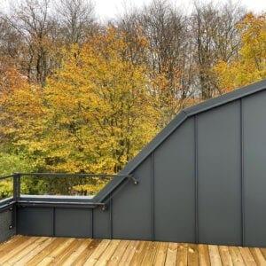 Tillbyggnaden i antracitgrå aluminiumplåt med takterassen och Skrylleskogen i bakgrunden. Syns gör också den snedskurna dörren in till sovloftet.